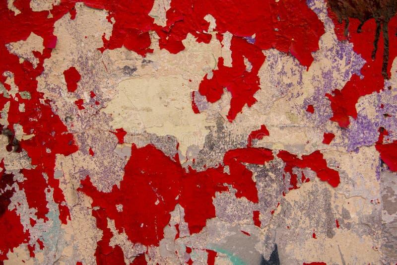 Oude witte grijze geslagen concrete muur met het pellen van heldere rode verf Ruwe Oppervlaktetextuur stock fotografie