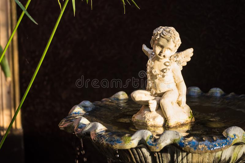 Oude witte van de het beeldhouwwerkzitting van de engelencupido het waterfontein royalty-vrije stock afbeelding