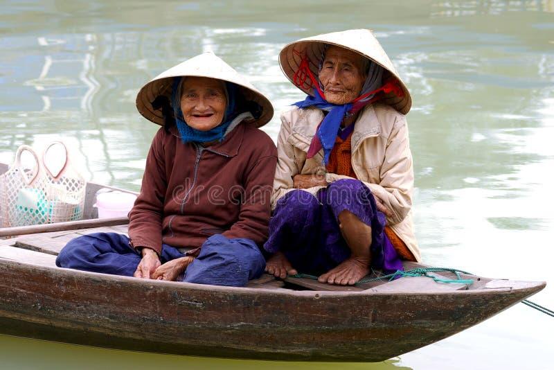 Oude womans in een boot op een straat in Hoi, Vietna stock afbeeldingen