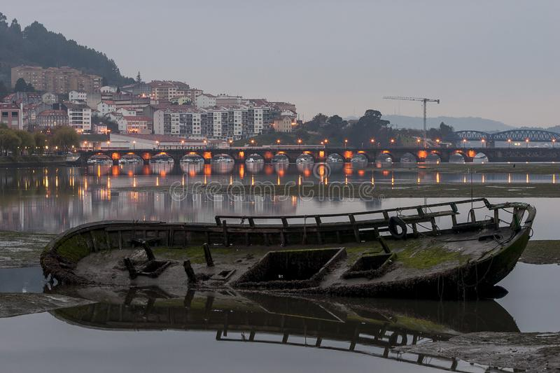 Oude Wooden Boat Decaying in the Sand at Eume River Pontedeume in Background with lighground with lighbridge La Coruña Galicia royalty-vrije stock afbeeldingen