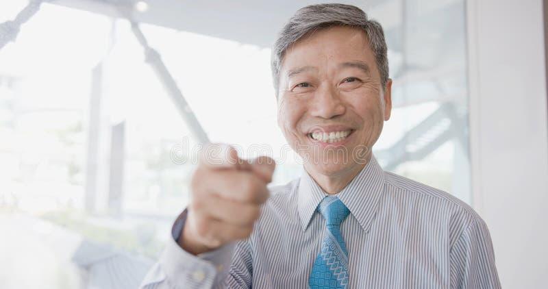 Oude zakenman die u richten stock afbeelding