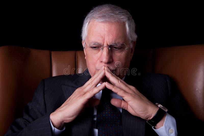 Oude zakenman gezet op een stoel, het denken stock afbeelding