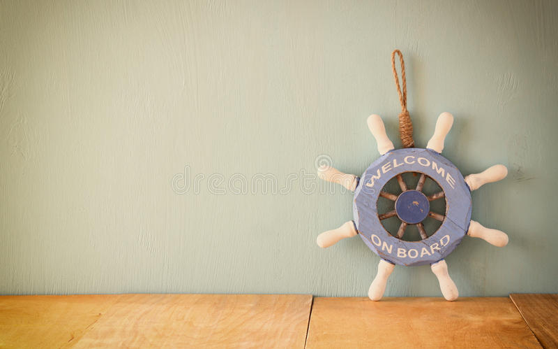 Oude zeevaart houten wiel, anker en shells op houten lijst over houten achtergrond wijnoogst gefiltreerd beeld stock fotografie