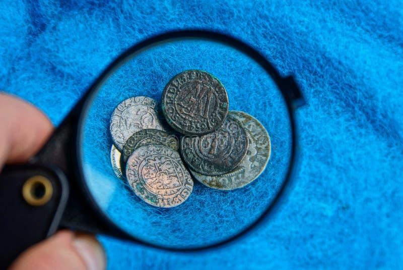 Oude zilver en kopermuntstukken onder een vergrootglas op een blauwe wollen stof stock foto's