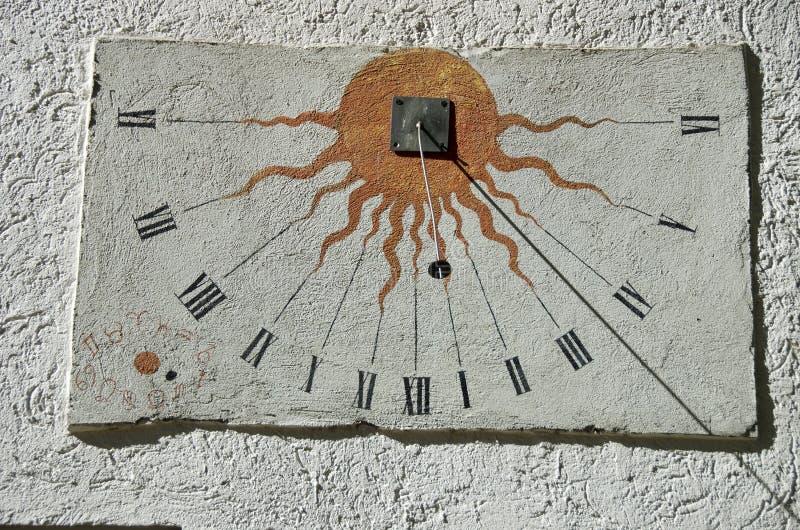 Oude zonnewijzer met tekens van de dierenriem op witte muur stock fotografie
