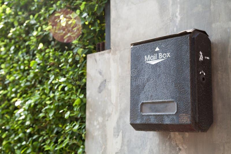 Oude zwarte bevlekte metaalbrievenbus op een grijze huismuur stock foto's