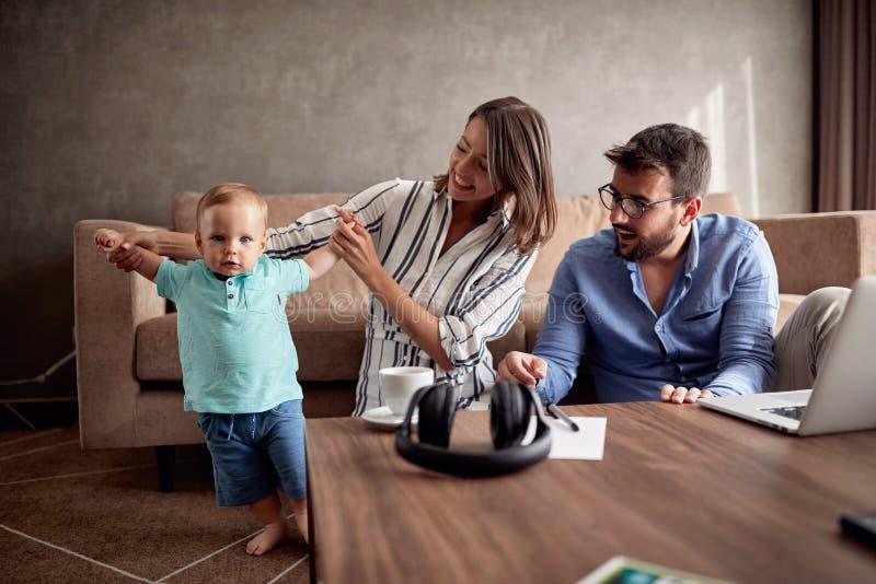 Ouder die gelukkige tijd thuis met hun babyzoon en playi doorbrengen stock fotografie