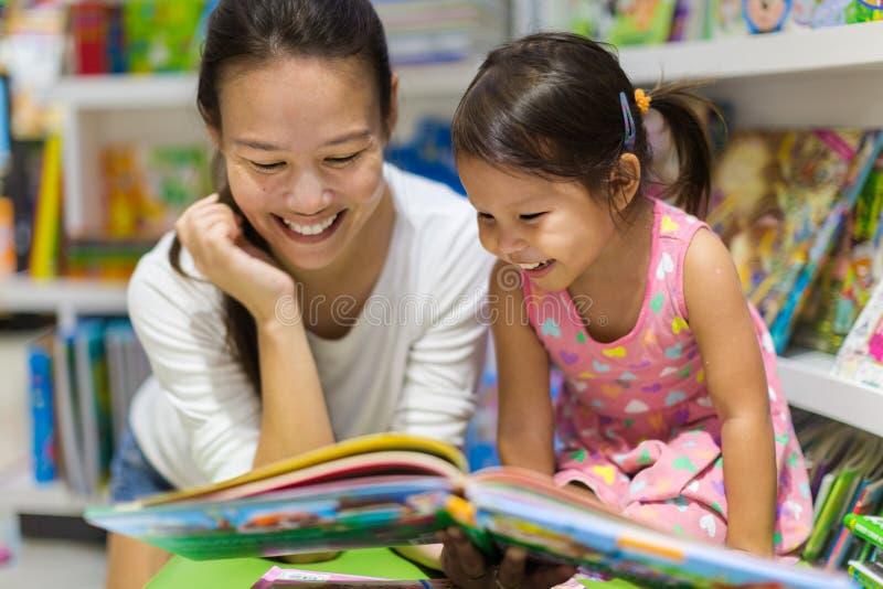 Ouder en kindlezingsboeken samen in de bibliotheek stock foto