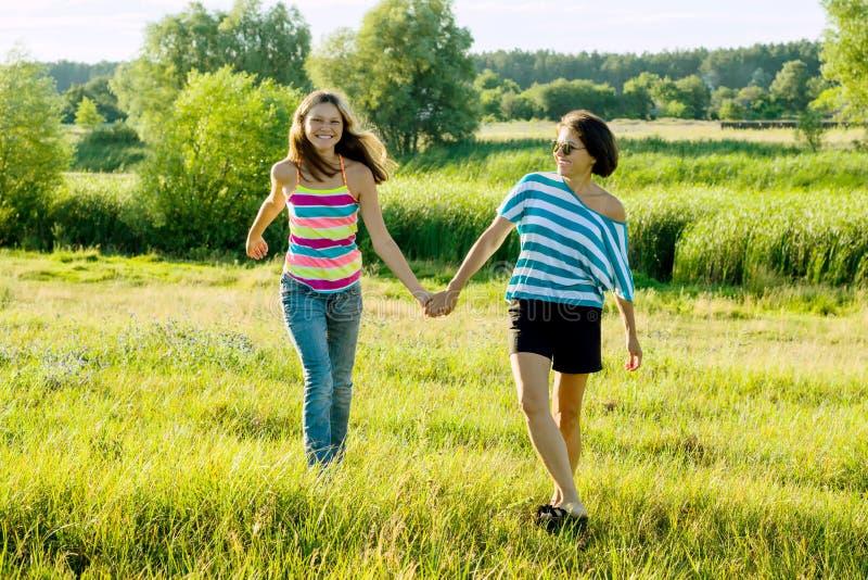 Ouder en tiener, Gelukkige moeder en tienerdochter 13, 14 jaar oude greephanden gaan lachbespreking royalty-vrije stock foto