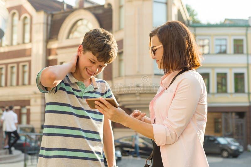 Ouder en tiener, verhouding De moeder toont haar zoon iets in de mobiele telefoon, is de jongen pijnlijk, het glimlachen, houdend royalty-vrije stock afbeeldingen