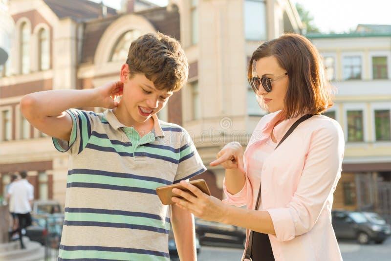 Ouder en tiener, verhouding Moeder en de zoon de tiener bekijken de mobiele telefoon, de achtergrond van de stadsstraat stock afbeelding