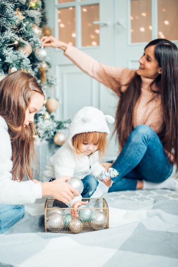 Ouder en twee kinderen die pret hebben en samen dichtbij Kerstboom spelen stock foto's