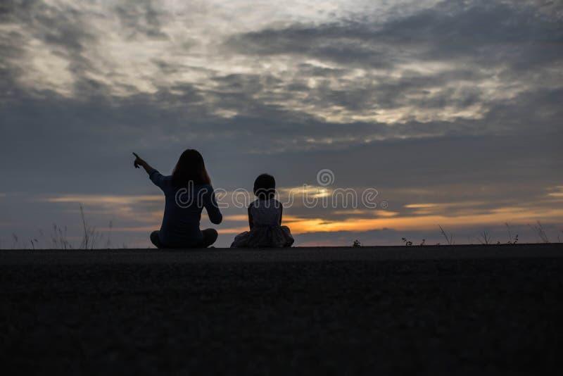 Ouder en zuster die op de zonsondergang letten royalty-vrije stock foto