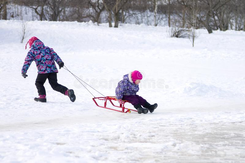 Ouder meisje die en haar jonge zuster op een slee op het ijs in sneeuw de winterpark in werking stellen trekken royalty-vrije stock foto's