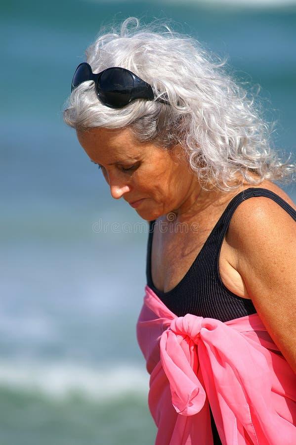 Ouder wijfje bij het strand royalty-vrije stock foto