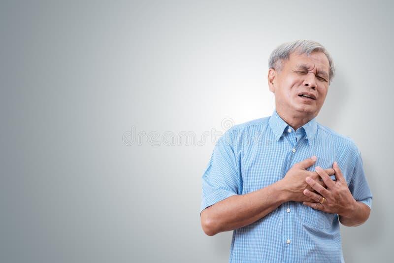 Oudere Aziatische mens die en de oorzaak van de borstpijn van hartaanval clutching hebben Hartkwaal bij de hogere mens met geïsol stock foto