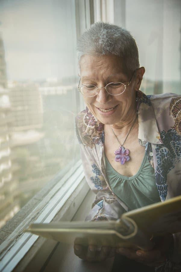 Oudere dame die door foto's kijken stock afbeelding