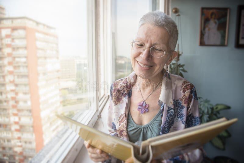 Oudere dame die door foto's kijken stock foto