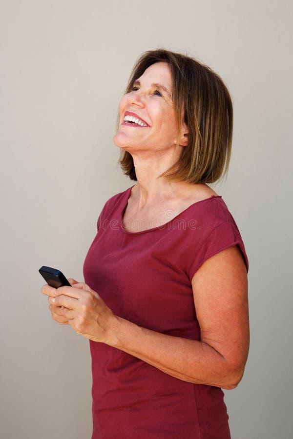 Oudere de cel van de vrouwenholding telefoon en het lachen stock foto's