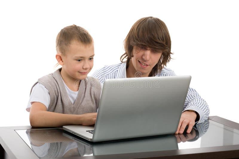 Oudere en jongere broers voor laptop stock foto