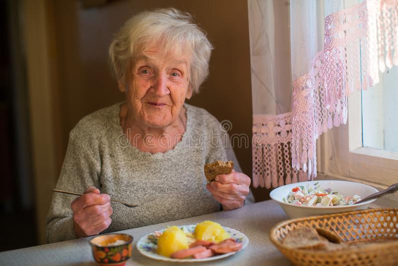 Oudere gelukkige vrouw die thuis bij de lijst eten royalty-vrije stock afbeeldingen