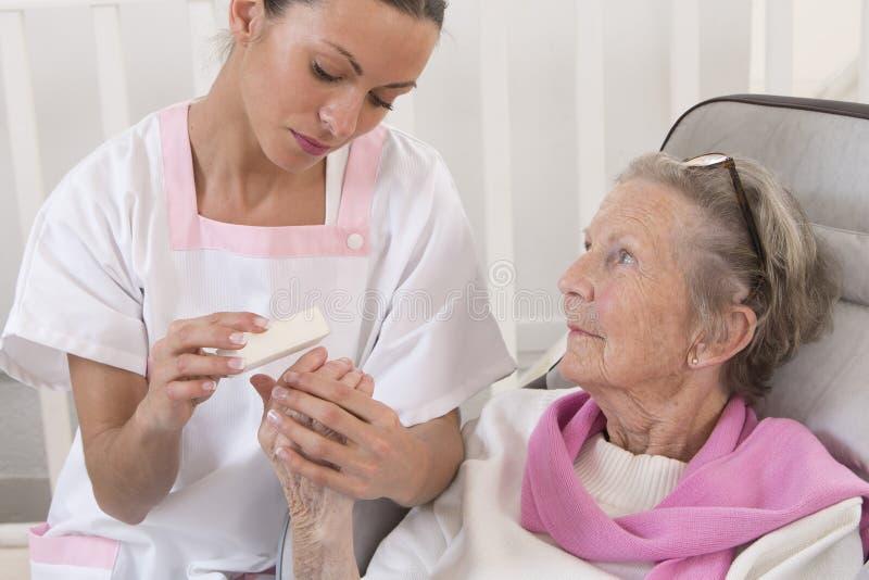 Oudere hogere vrouw die de behandeling van de huisschoonheid ontvangen stock foto's