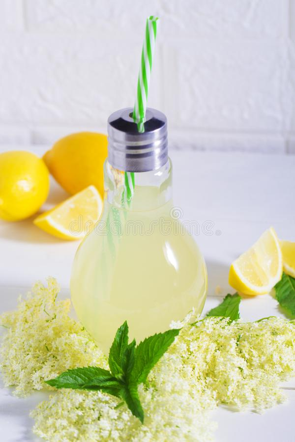 Oudere limonade - gezonde en verfrissende de zomerdrank Sluit omhoog van eigengemaakte elderflowerstroop in een fles met oudere b stock foto