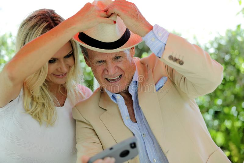 Oudere man die een selfie met een jongere vrouw voor sociale media nemen stock afbeeldingen