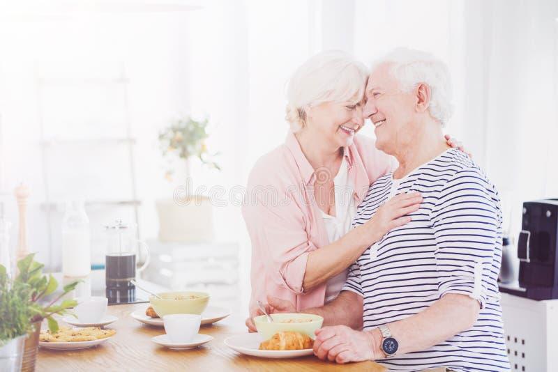 Oudere man en vrouw die in de keuken koesteren stock foto
