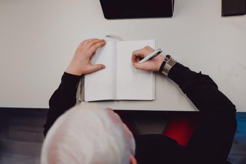 Oudere mens bij het bureau die in zijn notitieboekje schrijven royalty-vrije stock afbeeldingen