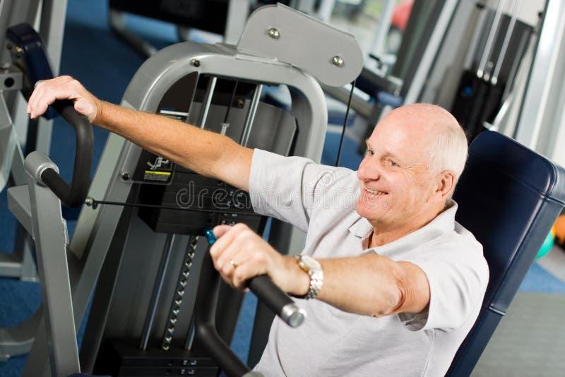 Oudere mens die bij de gymnastiek uitoefent stock foto