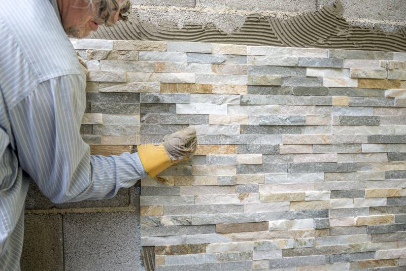 oudere mens die een muur met siertegels verfraaien stock afbeelding afbeelding bestaande uit. Black Bedroom Furniture Sets. Home Design Ideas