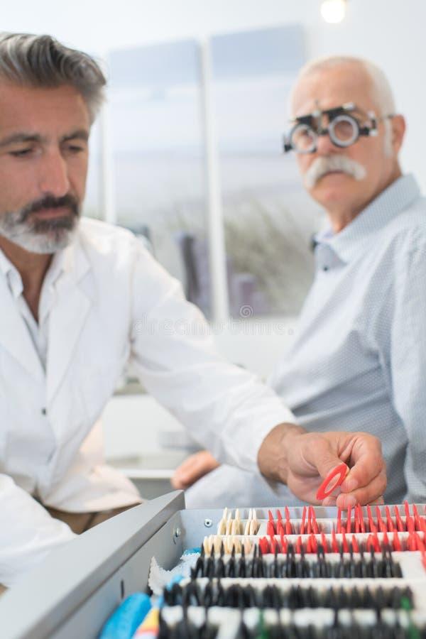 Oudere mens die het onderzoek van de oogtest nemen stock foto's