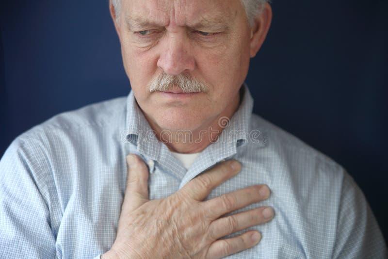 Oudere mens die pijn in borst voelt royalty-vrije stock afbeelding