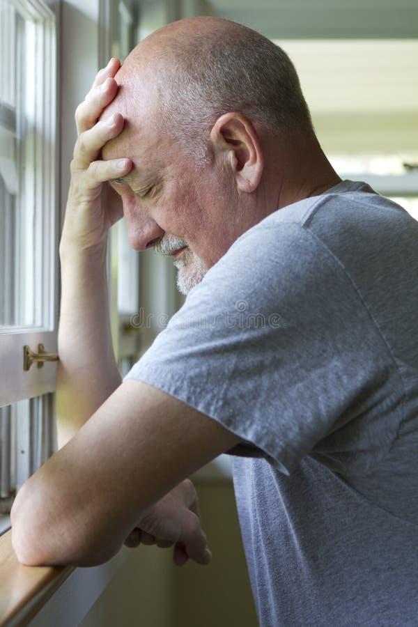 Oudere mens die pijn of depressie uitdrukken stock foto's