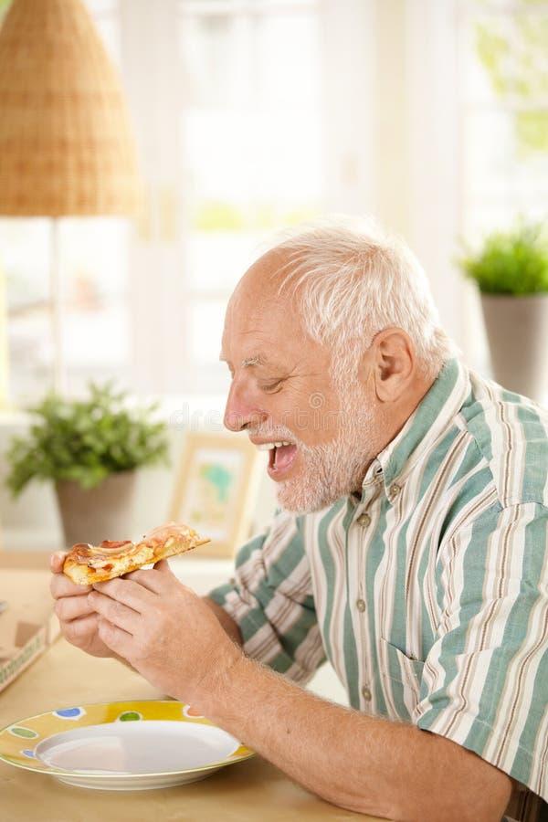 Oudere mens die pizzaplak thuis eet stock foto's