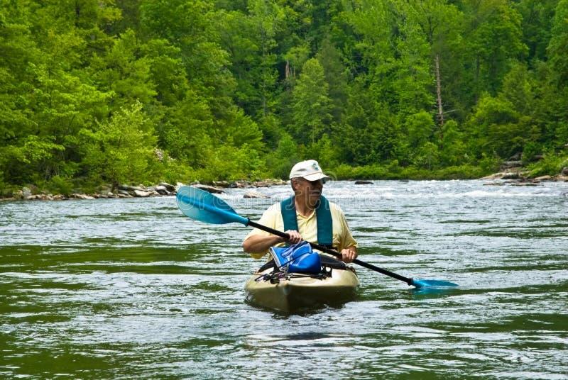 Oudere Mens Kayaking/de Stroomversnelling van de Rivier stock foto