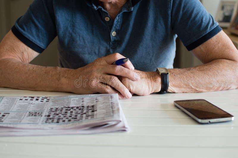 Oudere mens met kruiswoordraadsel en telefoon royalty-vrije stock foto