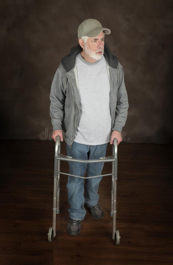 Oudere Mens met Walker On Brown Looking Off-Camera royalty-vrije stock afbeelding
