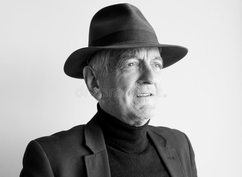 Oudere mens in zwarte hoed stock afbeeldingen