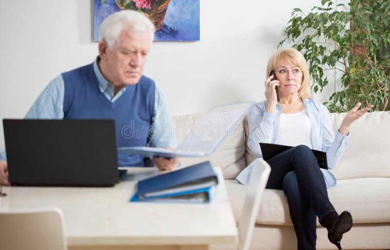 Oudere mensen die thuis werken royalty-vrije stock afbeelding