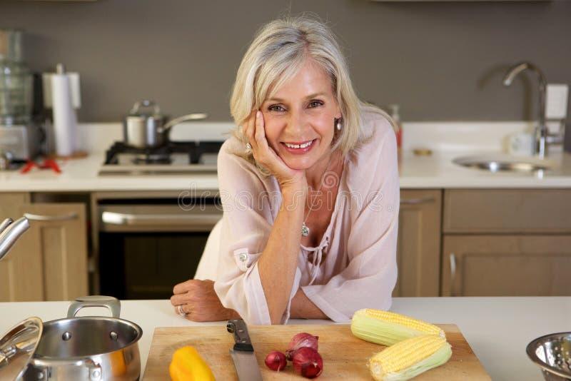 Oudere mooie vrouw die op keukenteller leunen met vers product stock foto's