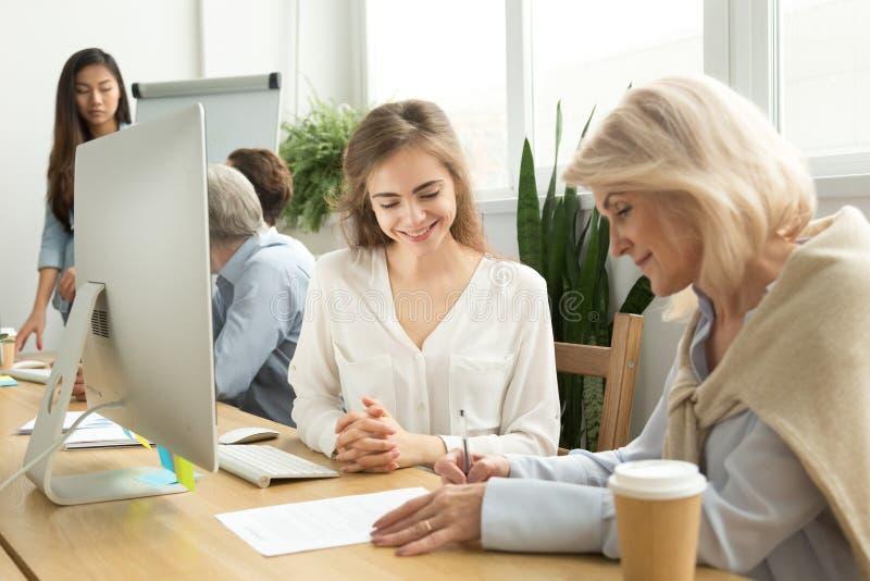 Oudere onderneemster die contract met glimlachende vrouwelijke manager ondertekenen royalty-vrije stock afbeelding