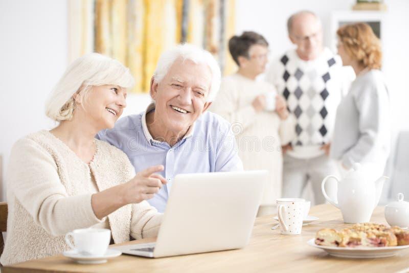 Oudere paarzitting bij laptop royalty-vrije stock afbeelding
