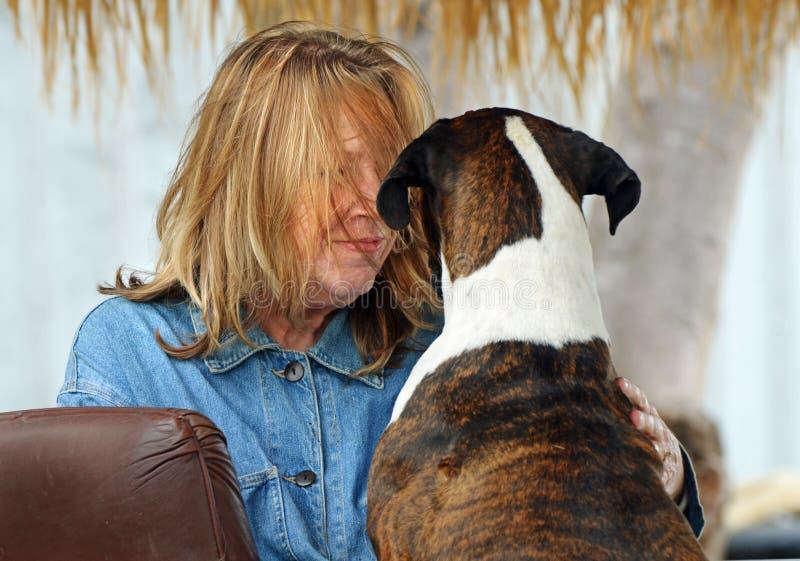 Oudere rijpe vrouw en haar beste & vriendenhond die koesteren spreken royalty-vrije stock fotografie