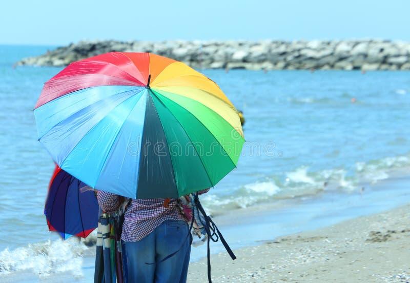 Oudere venter van kleurrijke paraplu's door het overzees op het strand in s stock afbeeldingen