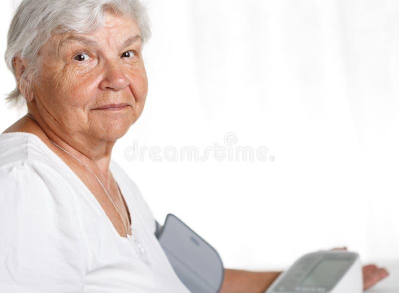 Oudere vrouw die bloeddruk meten stock afbeelding