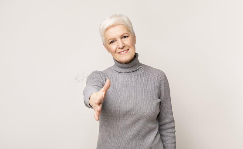 Oudere vrouw die de hand breidt voor handdruk op camera royalty-vrije stock fotografie