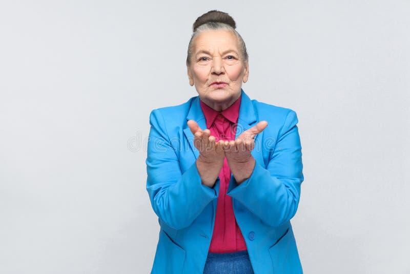 Oudere vrouw die luchtkus verzenden bij camera stock fotografie