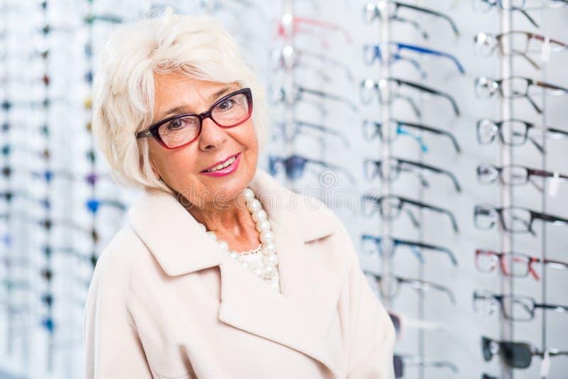 Oudere vrouw die op glazen proberen stock afbeelding